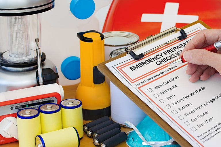 "alt=""A person with a clipboard with a checklist of Emergency items going through items on a table."""