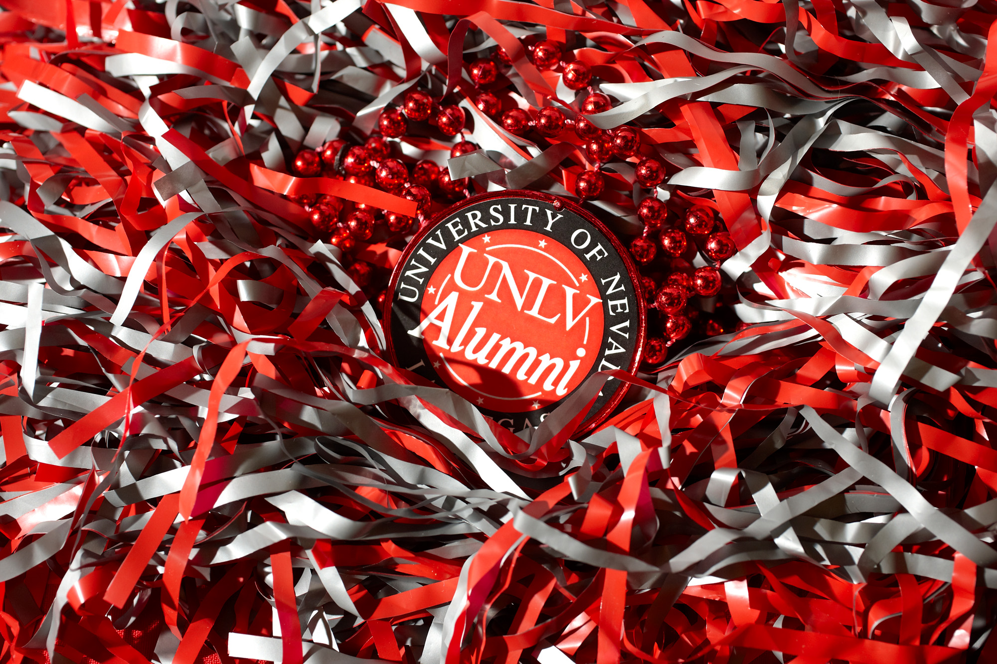 A UNLV Alumni badge surrounded by red and gray confetti.