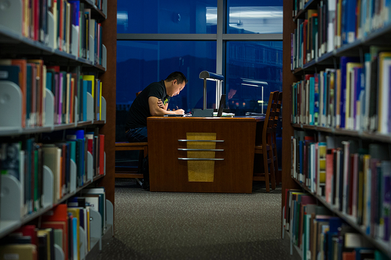 A male student studying at the library.