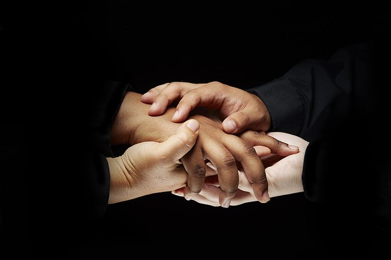 Close up of two people holding hands with dark background.