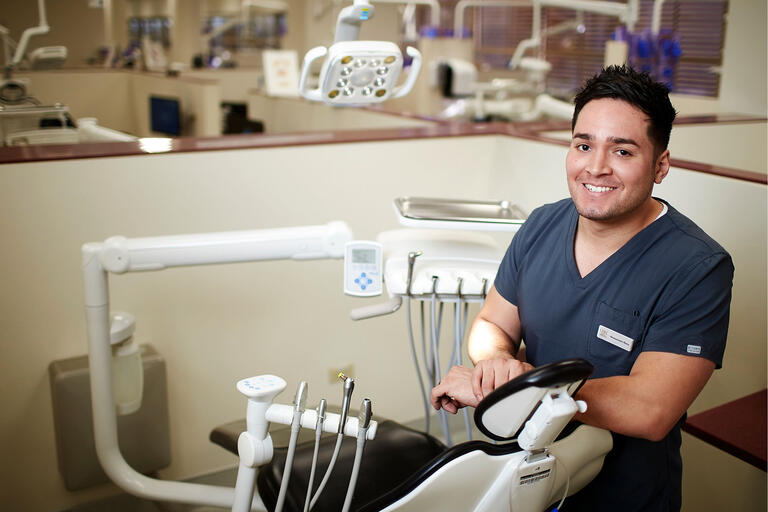 Allesandro Retis leaning on dental examine chair at UNLV School of Dental Medicine.