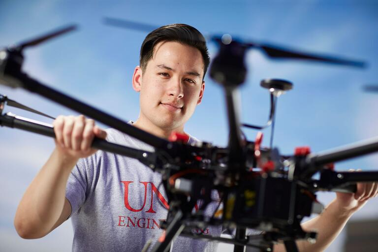 Male with a U-N-L-V t-shirt holding a drone.