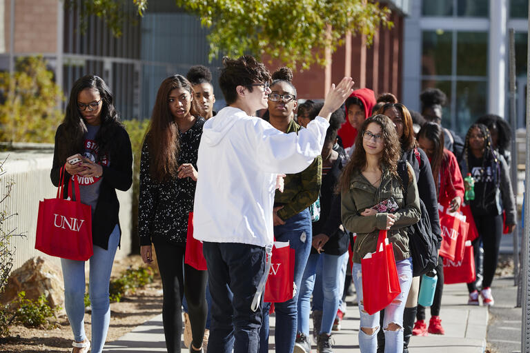 A UNLV student tour guide leads a group of Clark County School District students on a tour of UNLV's campus.
