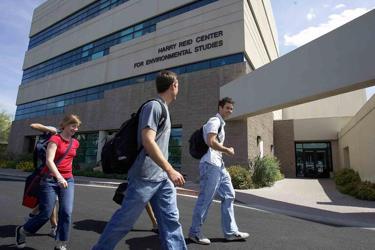 Three students walk past the Harry Reid Center building