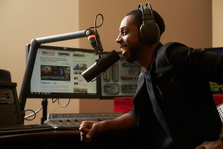 Student DJ speaks into a microphone