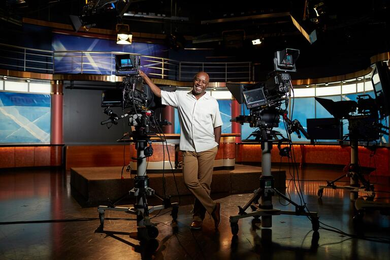 UNLV-TV employee poses next to television camera