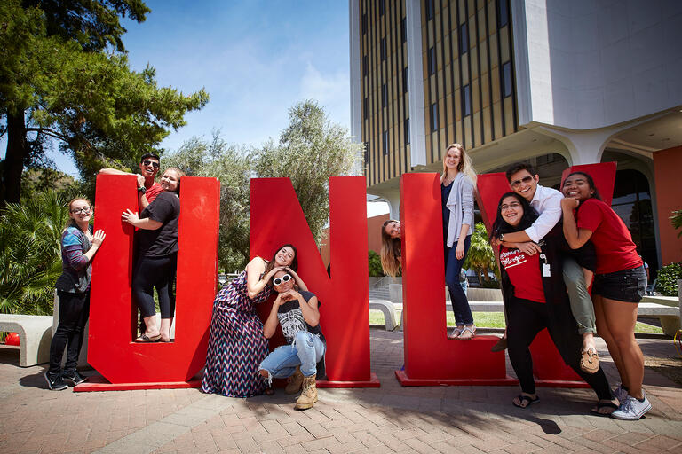 Students pose next to giant U-N-L-V letters